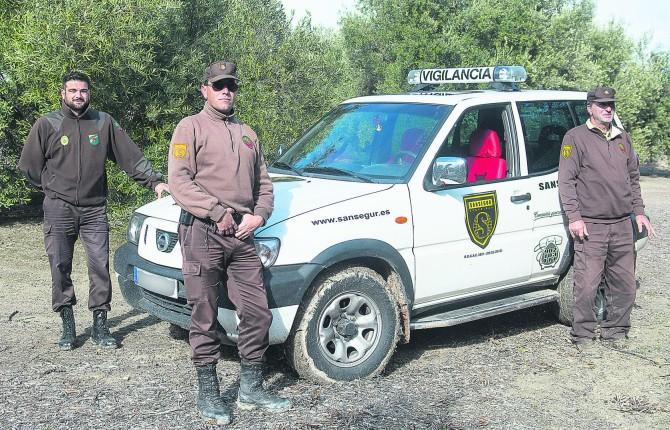 EN LAS FINCAS. Tres de los vigilantes de seguridad contratados por los cooperativistas de Úbeda posan con el vehículo todoterreno en un olivar durante las labores de vigilancia.