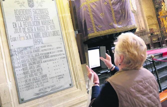 """MEMORIA. Una mujer fotografía a una de las lápidas que recuerdan """"a los caídos"""" en el interior de la Catedral, en una foto de archivo."""